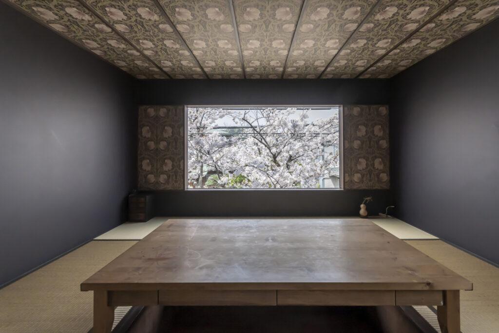 和室の大きなピクチャーウィンドウからの眺めは圧巻。ウィリアム・モリスの壁紙が桜をより美しく際立たせる。満開の桜がまるで額装された絵のよう。新緑の時期にはまた違った表情が楽しめる。