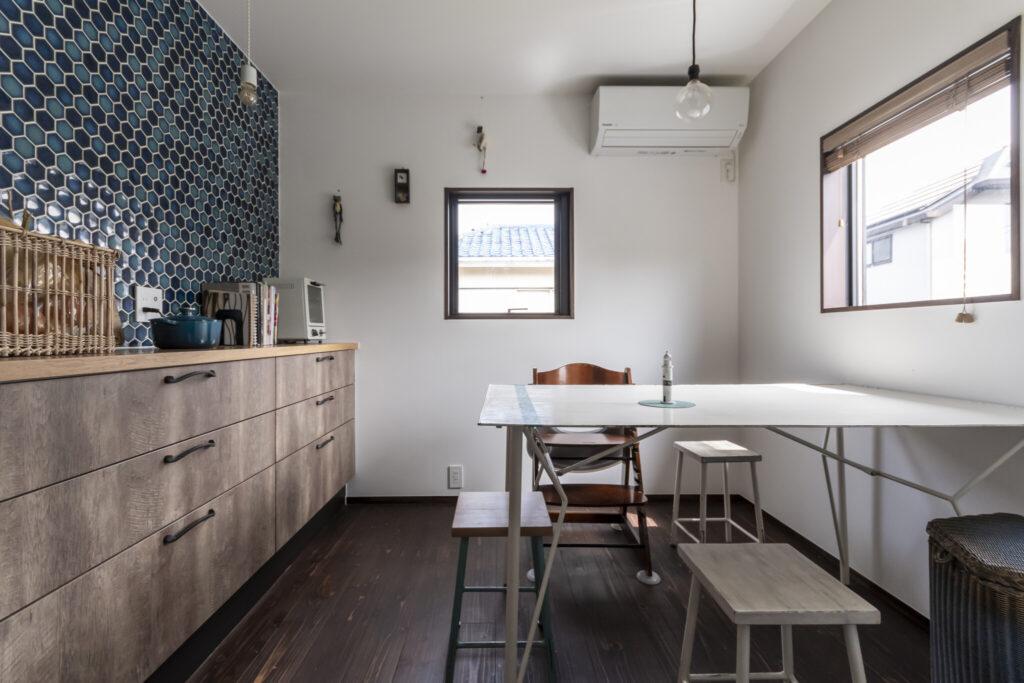 以前から愛用しているテーブルや椅子は、蚤の市で出会ったアイアンアーティストにオーダーしたもの。これに合わせて、壁面タイルはブルー系をセレクト。テーブル上の灯台も同じ作家のもの。
