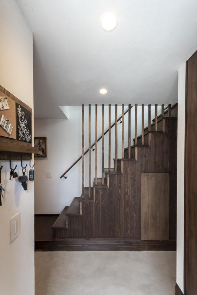 木製の縦格子がアクセントになった階段。側面につけたドアが可愛い。