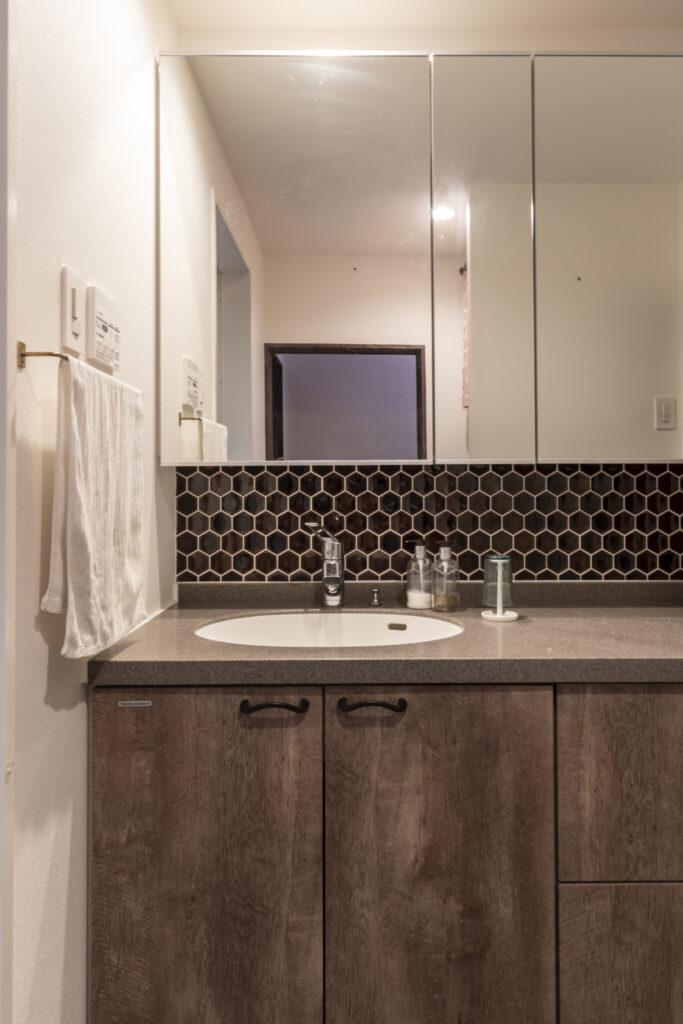 洗面台の立ち上がりのタイルはキッチンと色違い。左が浴室、右が家族用トイレ。2階にトイレを設けるスペースがなく、1階に2か所造った。「利便性より住んでいて楽しいほうを優先しました」(奥さま)。