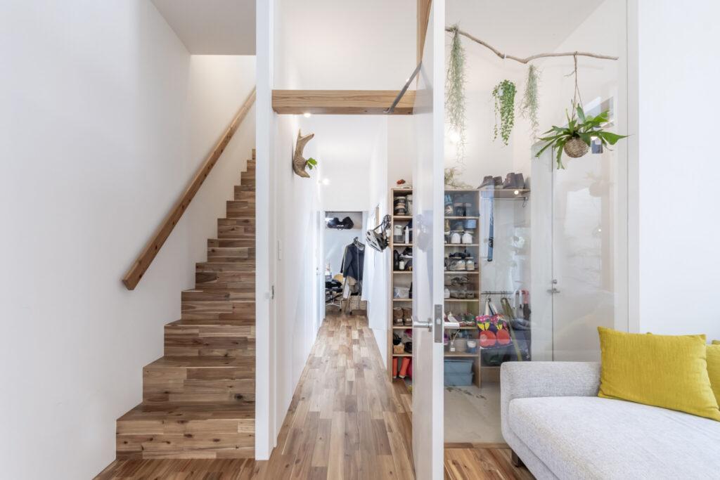 1階リビングから見る。右が玄関。奥に見えるのは夫婦でお互いの治療を行うためにリクエストでつくった部屋。左の階段はリビングから2階に上がりたいという希望からこの位置になった。