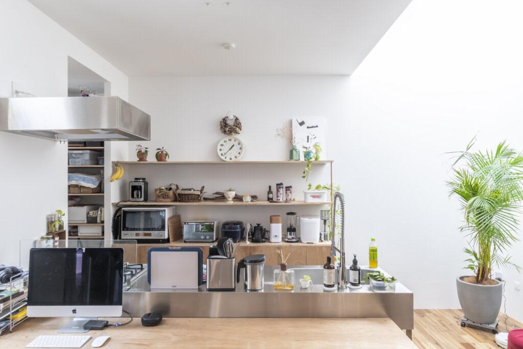 ステンレス製のキッチンは史恵さんが探して見つけた既製品。対面式にしたのは史恵さんのリクエストだった。壁の棚も史恵さんの希望で製作されたもの。右の南西コーナーは吹き抜けからの光で明るい。