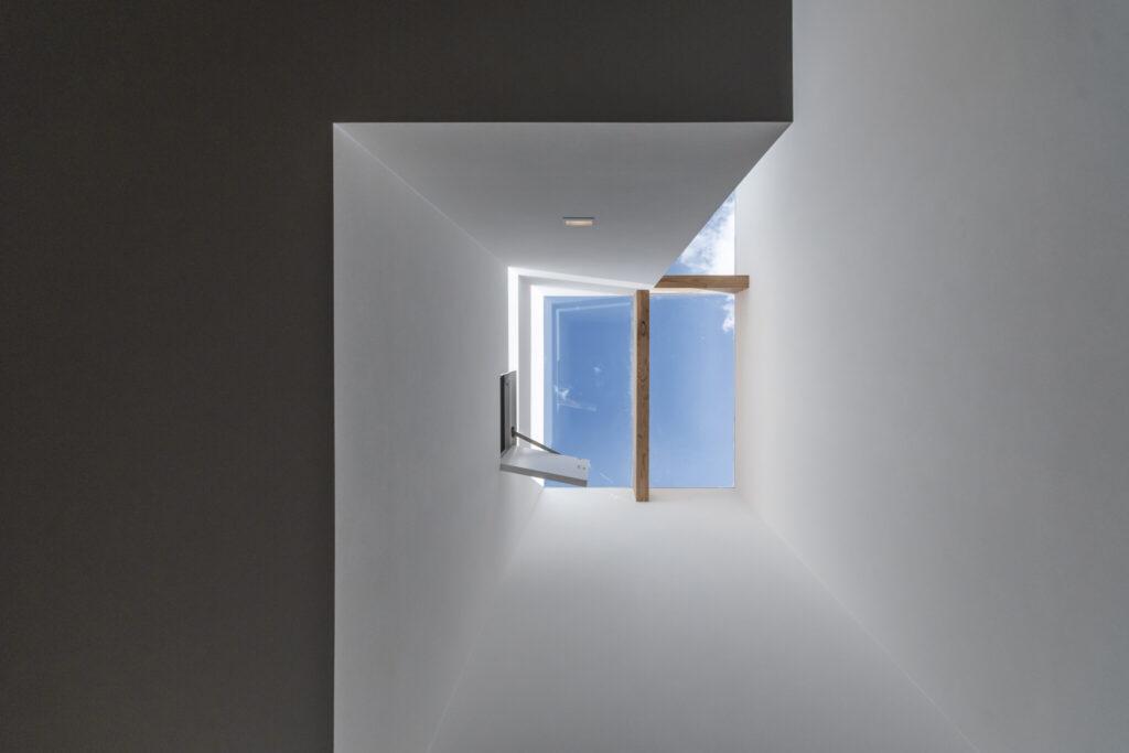 「吹き抜けが少しほしい」とのリクエストからつくられた南西コーナーの吹き抜けを見上げる。2階の寝室の小窓を開けると天窓から青空が見える。