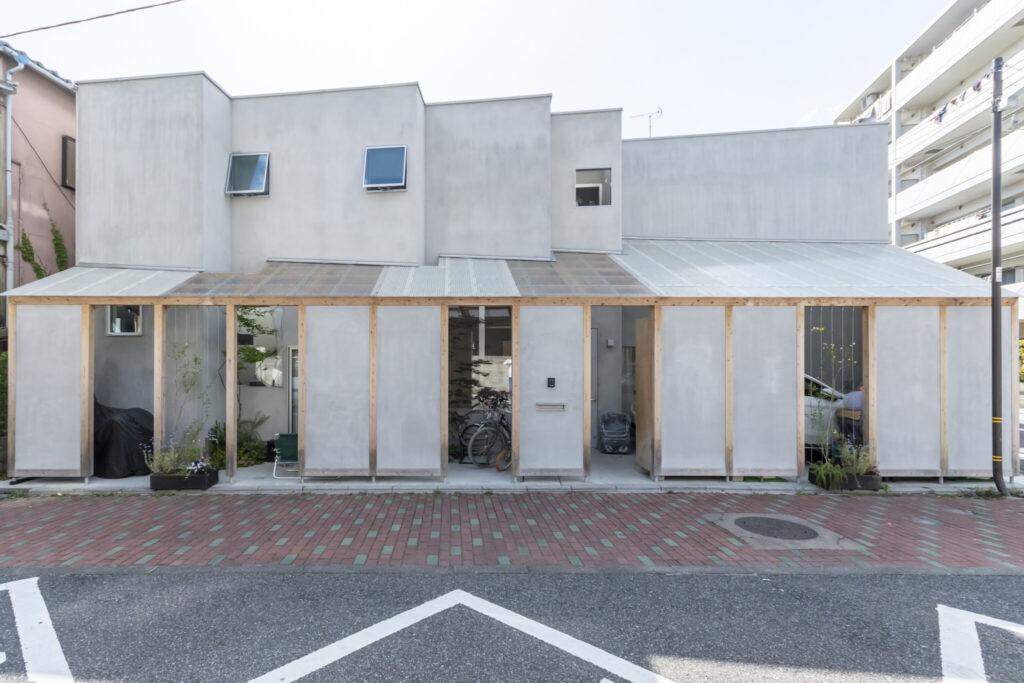 中間スペースの屋根ははじめ透明であったが、駐車場の車が日に焼けてしまうので乳白色にしてもらい、そこからこのように半透明板と交互の配置になった。手前のグレーの壁によってプライバシーが守られている。