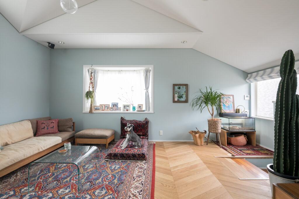 ペルシャ絨毯でソファのあるくつろぎスペースを作る。フローリングはヘリンボーンを採用。ソファはカーフのもの。ヴィンテージのガラスのコーヒーテーブルはロン・ハーマンで。
