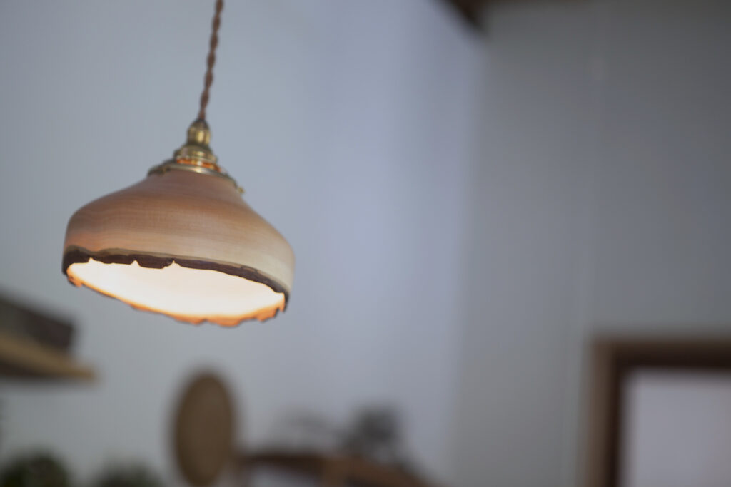 伐採したカツラの木で作製したランプシェードは、中矢嘉貴氏の作品。乾燥させず、生木を削って成形する独自の手法により、ゆがみやねじれなど豊かな表情が楽しめる。