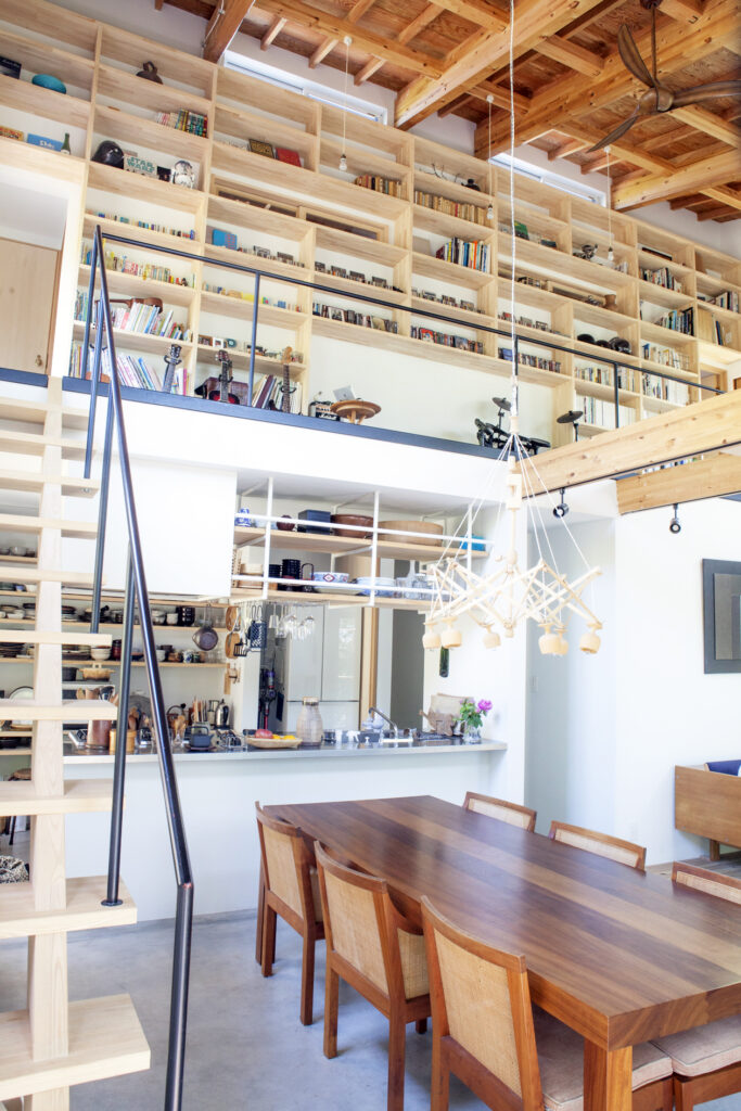 1階から見上げた高い天井は開放感いっぱい。2階の壁一面に造作した本棚は圧巻。本棚と天井の間に設けた窓により、熱がこもらず、空気が流れる。