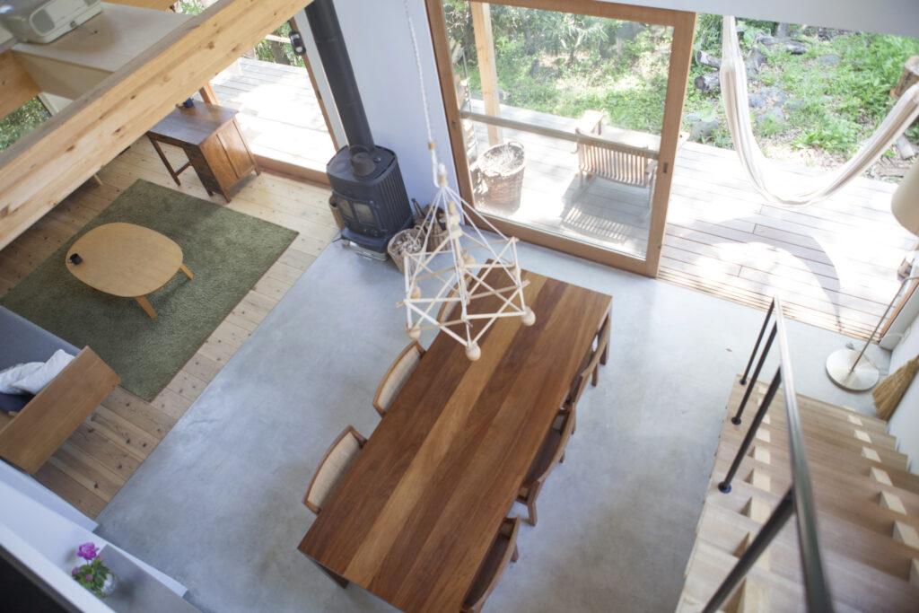 2階から1階を見下ろす。リビングの床は杉板、ダイニングはモルタル土間とし、ゆるやかにゾーニング。テラスまで一続きの大空間。