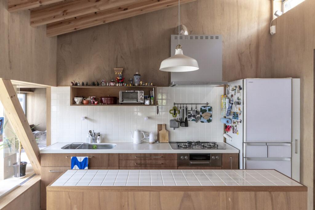 2階のキッチン。タイルを使うのはみづ江さんの希望だった。キッチンのコーリアンの白にあわせて白いタイルにした。棚の上が神棚兼フィギュア置き場として使われている。