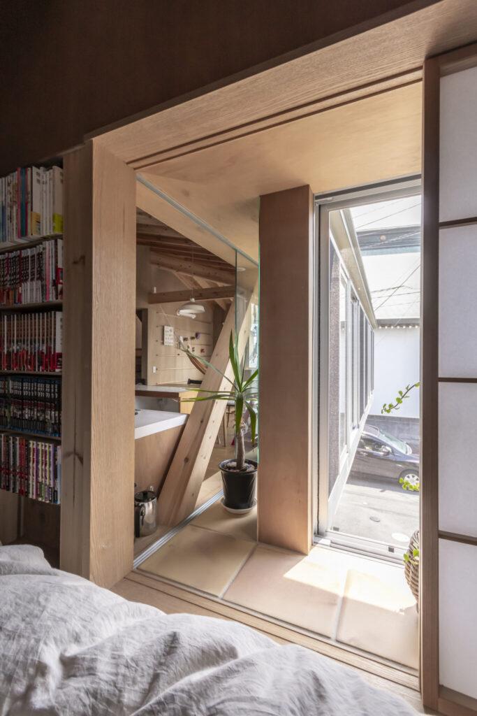 出窓の部分を介して手前の寝室とキッチンとがつながっている。