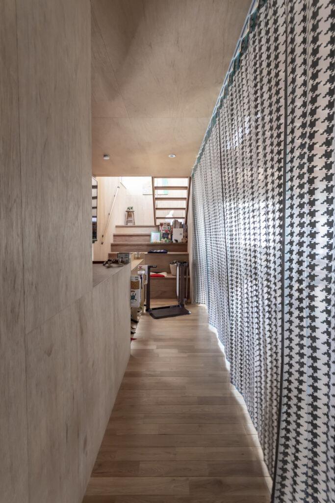 LDKと階段側をゆるく仕切るカーテンは安東陽子さんのデザイン。LDK側は鮮やかなブルー系の色が使われている。