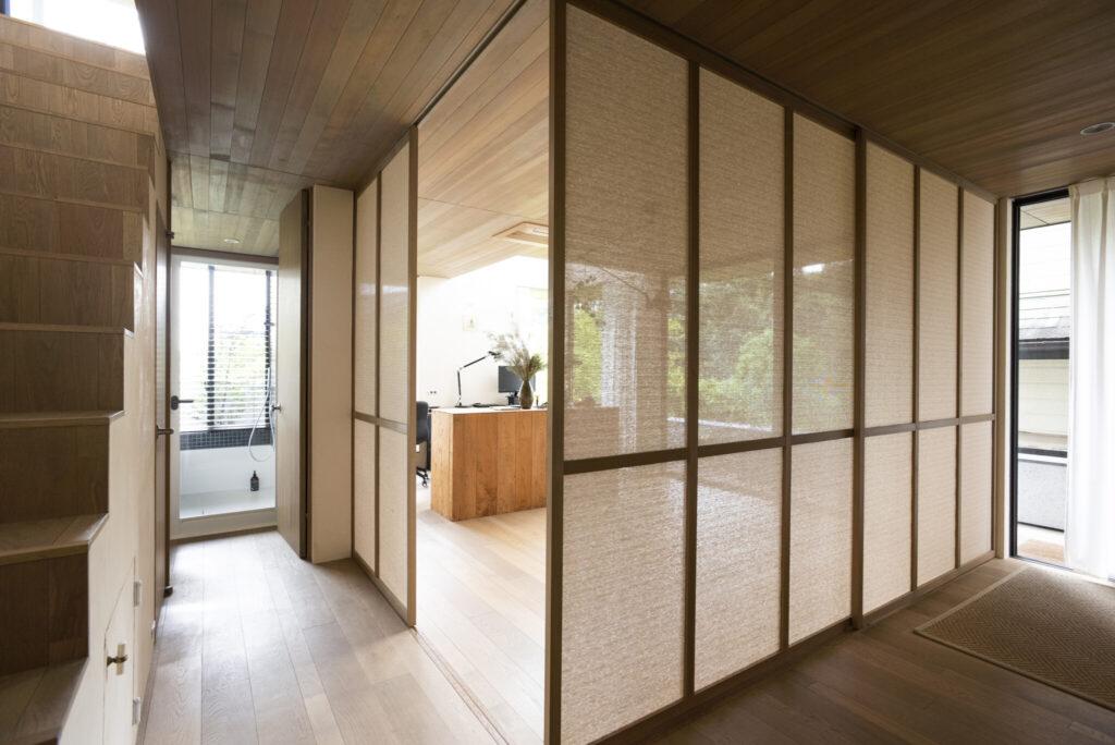 透過性のあるロールスクリーンの生地をはめ込んだ引き戸は、現場監督と青山さんで仕上げたもの。