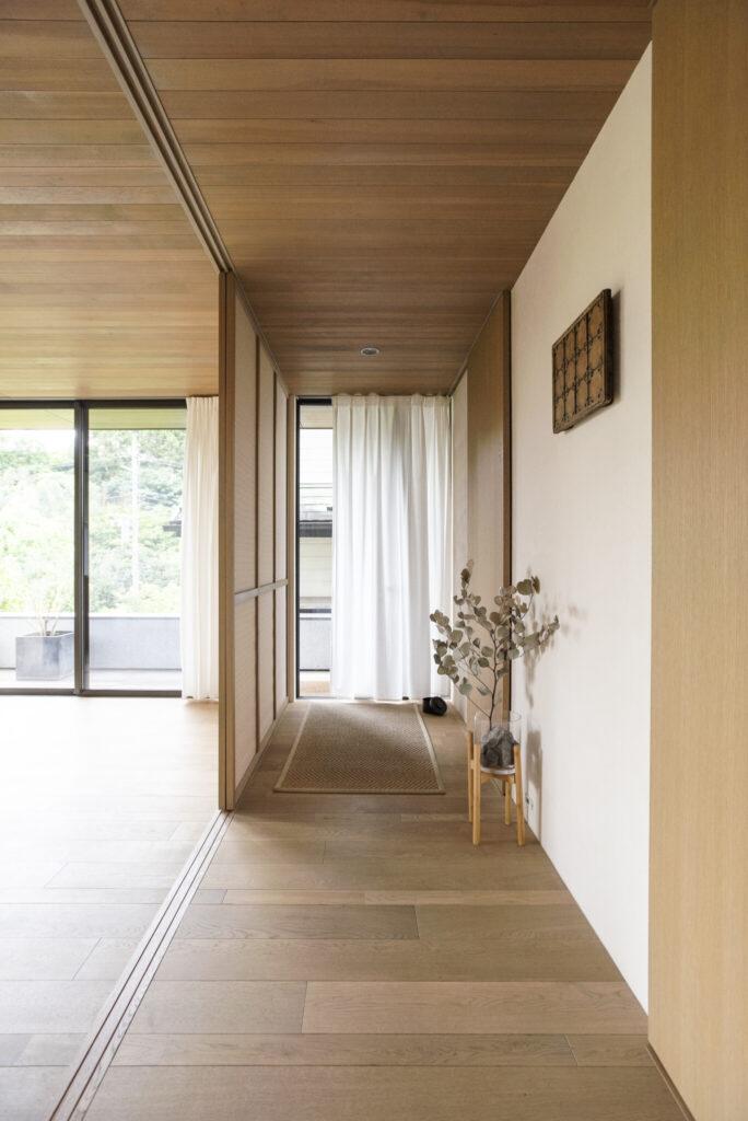 たたきを設けず、廊下と一体化した玄関はテラスドアを採用。オーク材の床は幅の広いタイプと細いタイプを組み合わせ、変化をつけた。
