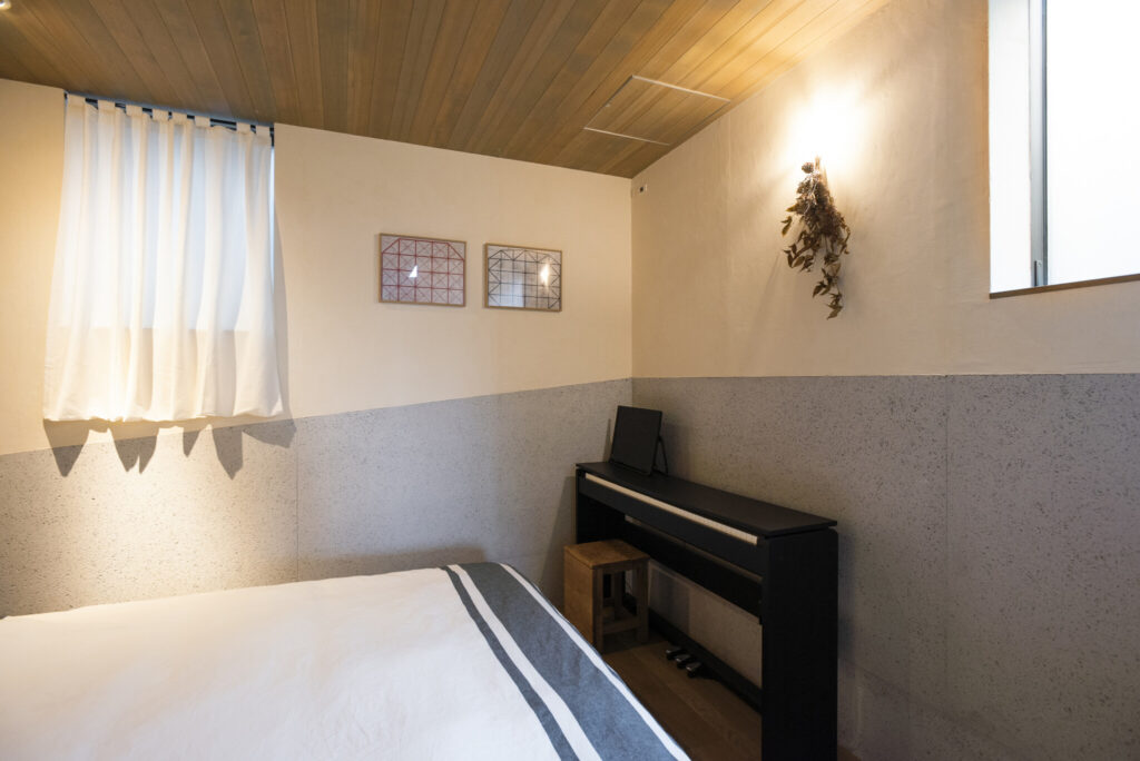 1階の寝室。壁下部に斜めに入ったグレーの木毛セメント板は、テラスにつけた外の手すり壁と同じ高さでデザイン。階段や2階の壁にも採用し、外と内のつながりをもたせた。