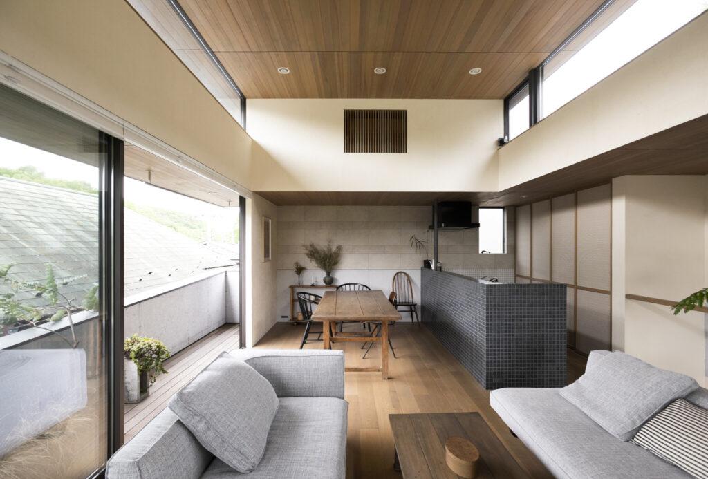 ブルーグレーのタイルに囲まれた対面式キッチン。「緑を眺めながらの調理は気持ちいいです」と隅谷さん。ゆったりとしたソファは『HUKLA』。