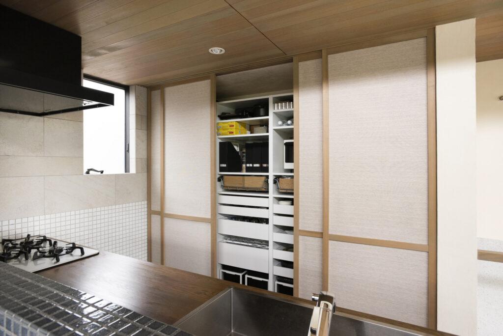 キッチン背面の引き戸内には、冷蔵庫や洗濯機など生活感の出る家電をすべて収納。『IKEA』の食器棚や収納グッズを使用し、無駄なく整理整頓。
