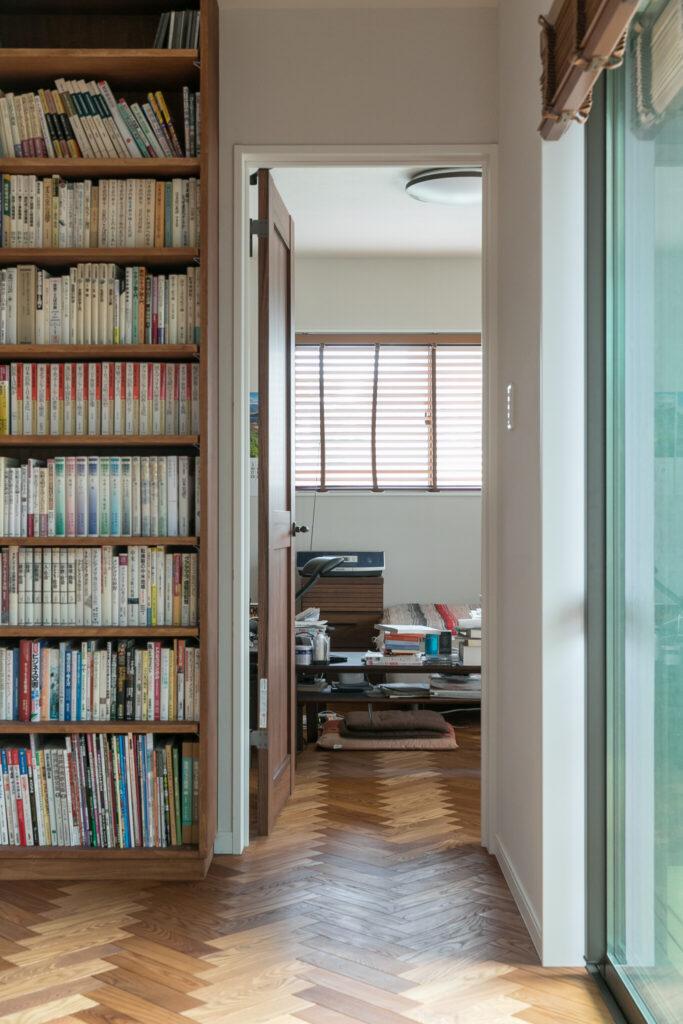 2階には2人の寝室があり、本棚の奥が山田さんの部屋。右側の掃き出し窓は2階のウッドデッキに繋がっている。