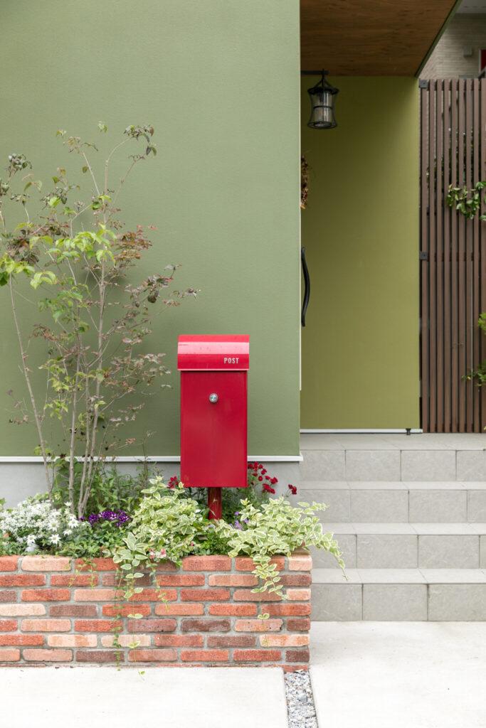 緑の外壁と相性抜群な赤いポスト。玄関前の花壇も充実している。