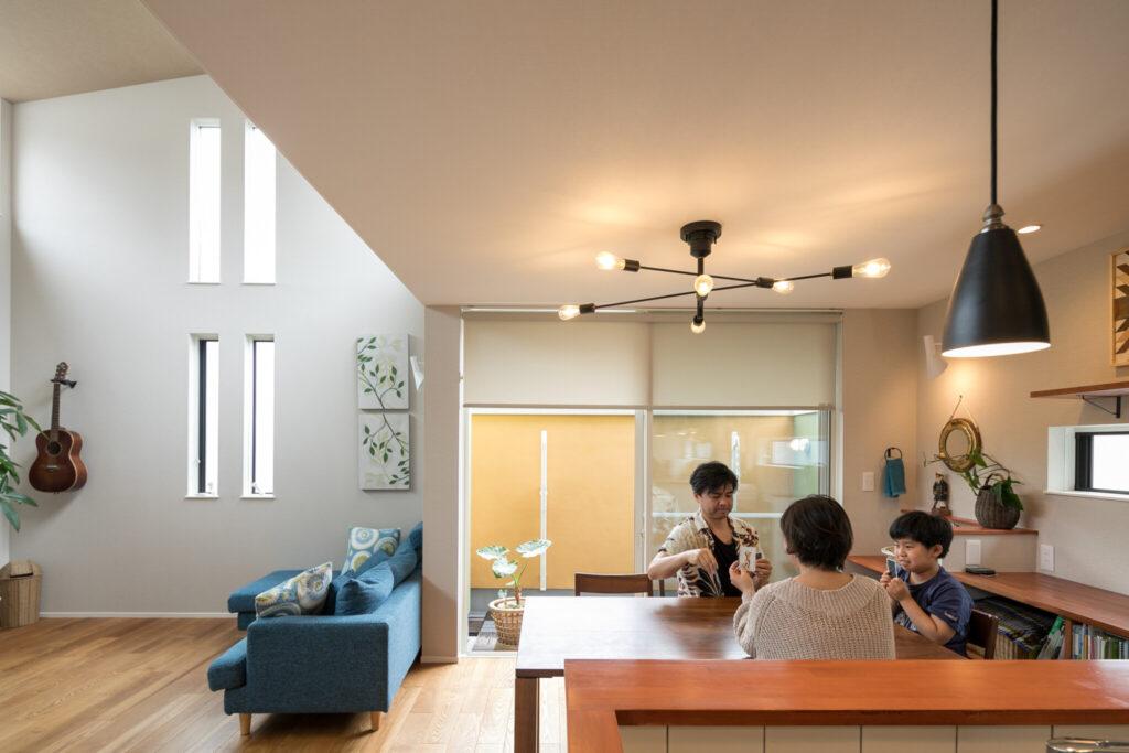 キッチンから正面を見る。青いソファやバルコニーの黄色い外壁とモダンな照明器具が絶妙にマッチする。