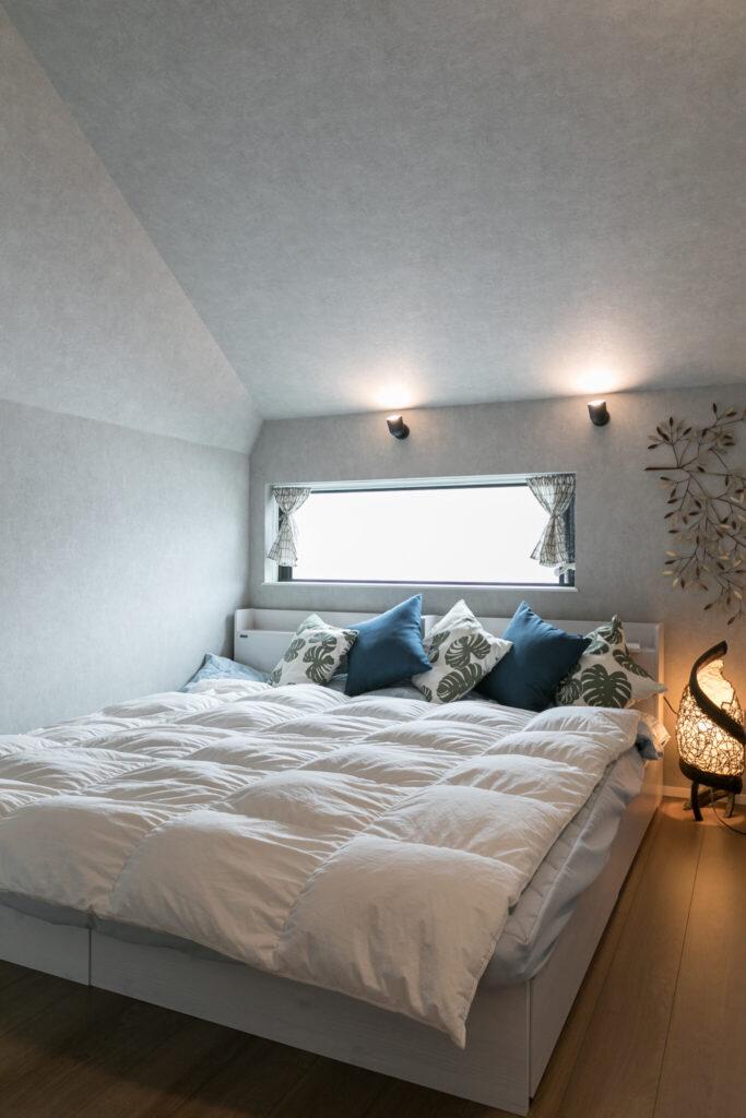 夫妻の寝室。屋根の形状を活かした勾配天井によって、こもり感のある落ち着ける空間に。