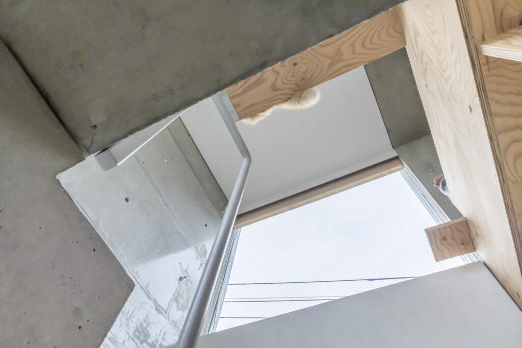 2階への階段途中から見上げる。右下はネコが窓まで移動するために設けられた出っ張り。上にしし丸の尻尾が見える。