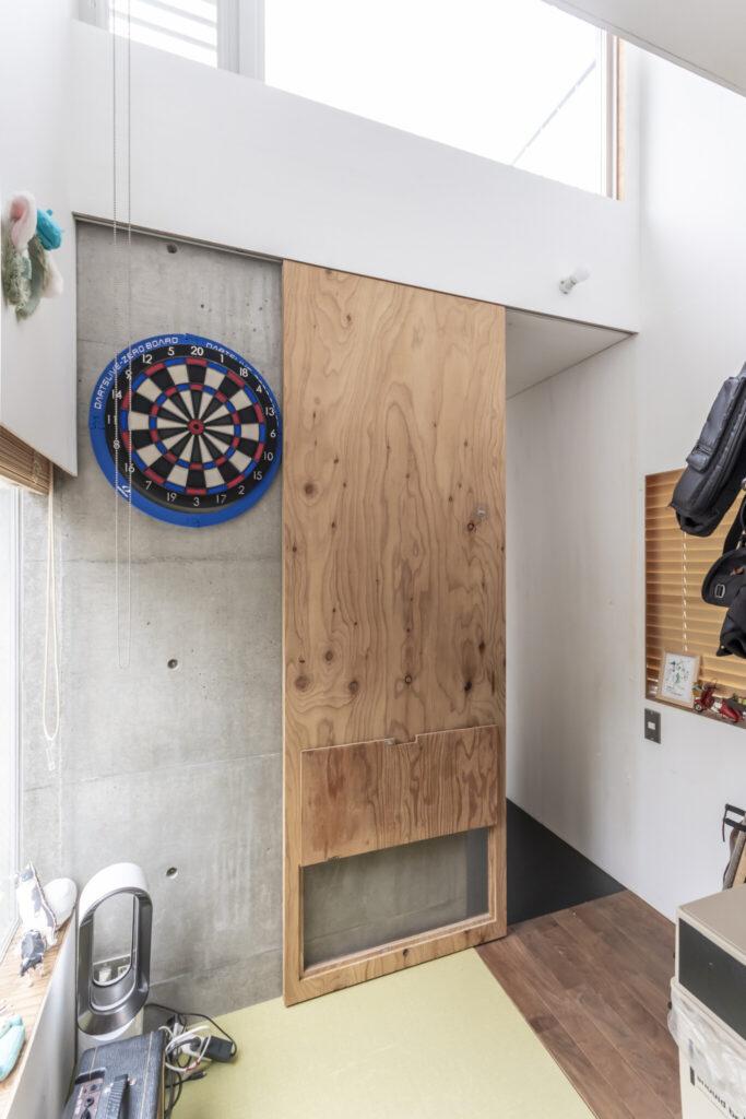 息子さんの個室。ふだんはネコが入らないように扉を閉めているため下部を空気が通るように開けられる。吹き抜けの向こうがテラスになっている。