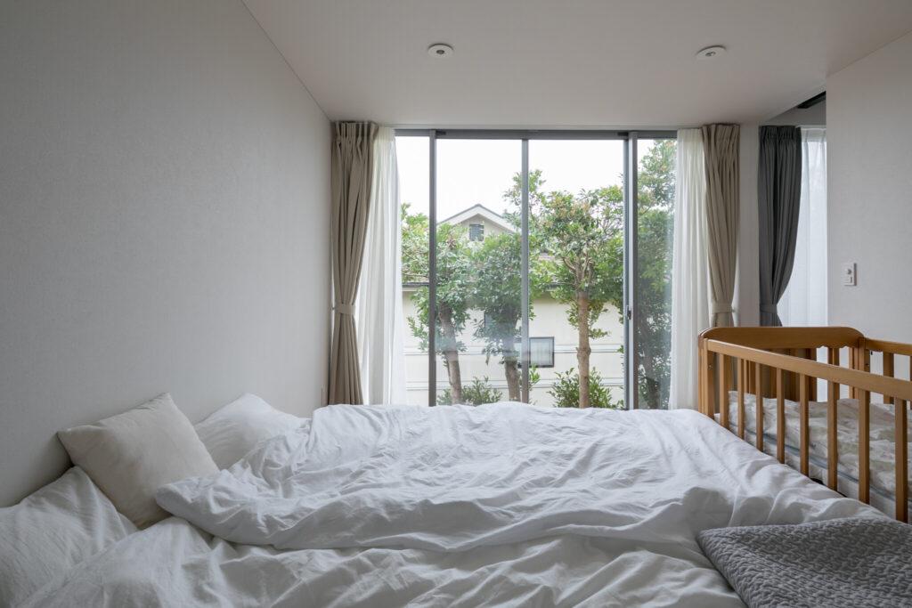 シンプルな設えの1階寝室。裏庭に面した開口から入る光によって、心地よい明るさに。