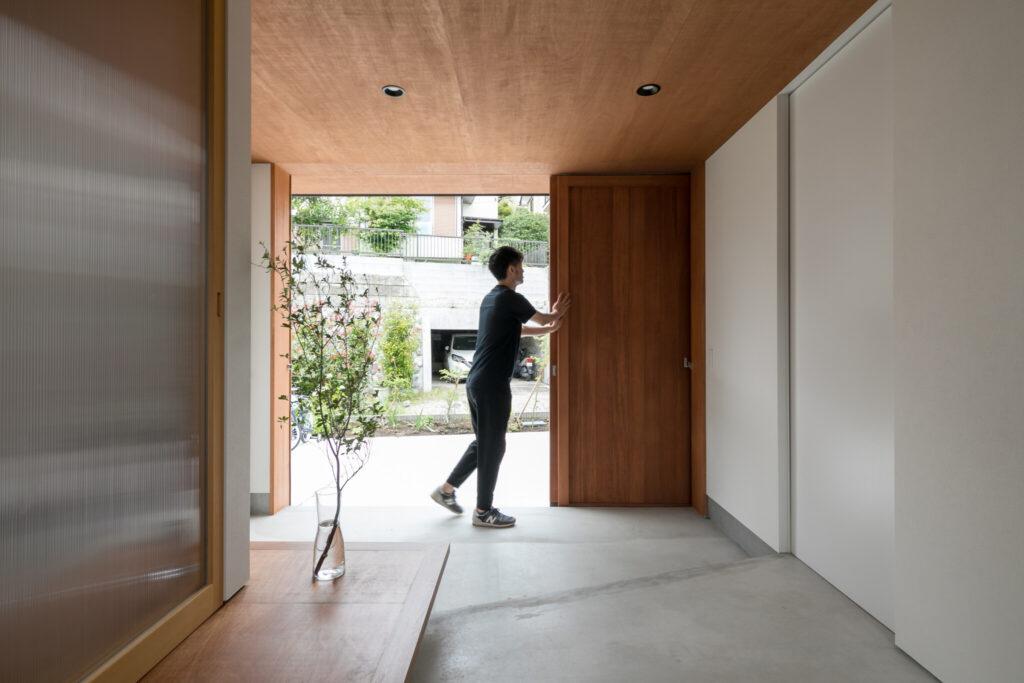 北側の玄関引き戸を全開にすることで、前庭と室内が連続する空間とした。