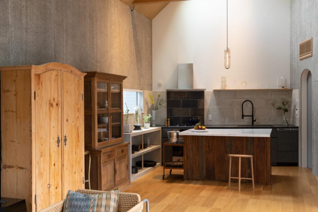 グレーの木毛セメント板や濃淡のタイルを採用した壁が、オーダーしたキッチンカウンターたちを引き立てる。