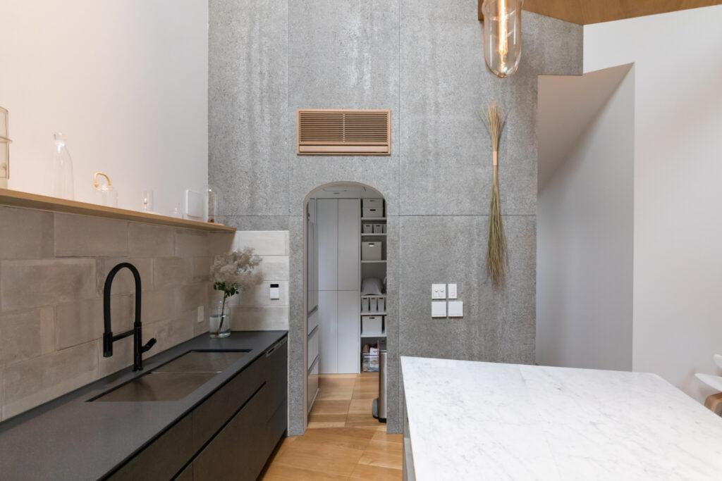 アーチ型の開口の奥はパントリー。「冷蔵庫や生活感のあるものは見せたくないため、扉をつけてもらいました」(未来さん)。壁付けのカウンターの天板は機能性を考えて人工大理石に。