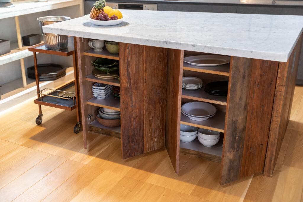 天板は大理石、面材にフローリングの古材を使用したカウンターは、空間の形状に合わせて台形に。「ホームパーティの時など、自由に取り出せるように」(未来さん)とリビング側には客用の食器を収納。