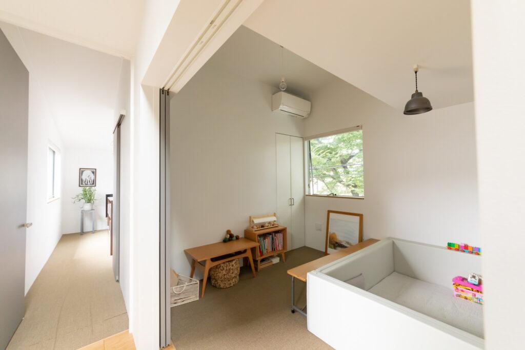 寝室(奥)と子ども部屋には、麻の床材を採用。「素足に気持ちいいです」と啓太さん。子ども部屋に置かれた木製家具(壁側)は『マルニ木工』。サークルの中で遊ぶのが詩梛ちゃんのお気に入りとのこと。
