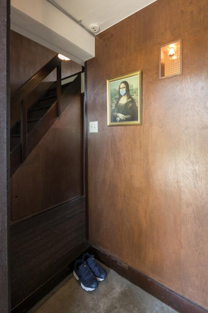 玄関の明かりは、壁の向こうのトイレの明かりと共用。時代を感じさせる仕様だ。モナリザはマスク着用(笑)。