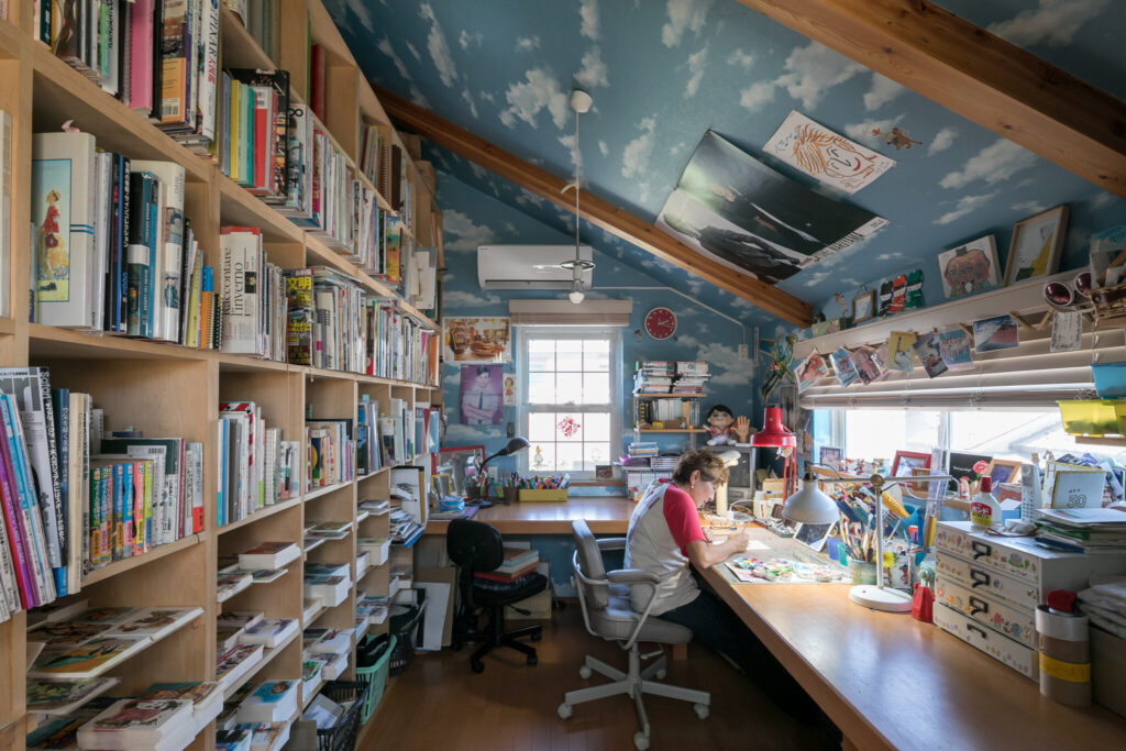 アトリエ。左側にある天井いっぱいの造作棚には資料が並ぶ。壁紙はアメリカの有名なアニメ作品をイメージして選んだ。