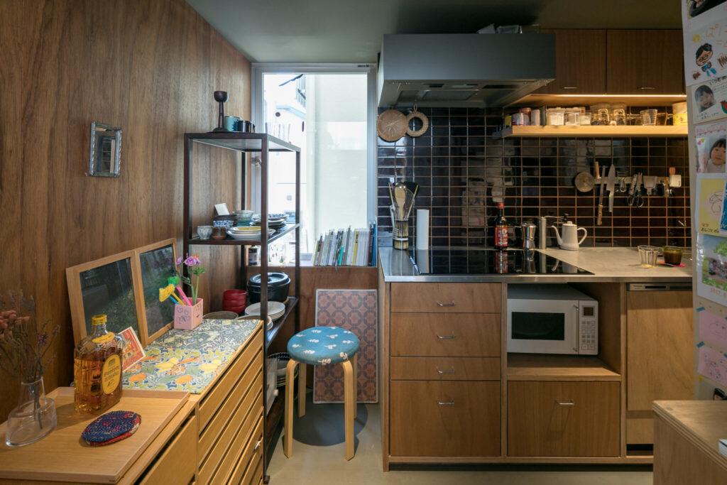 リビングから50cm下げた位置にあるキッチンは、にじり口から中に入っていくような感覚。天井が低く、籠もる感じが心地よい。タイルは光を反射するものを選び、横の窓は住宅地の奥まで見通せる場所を狙って開けている。