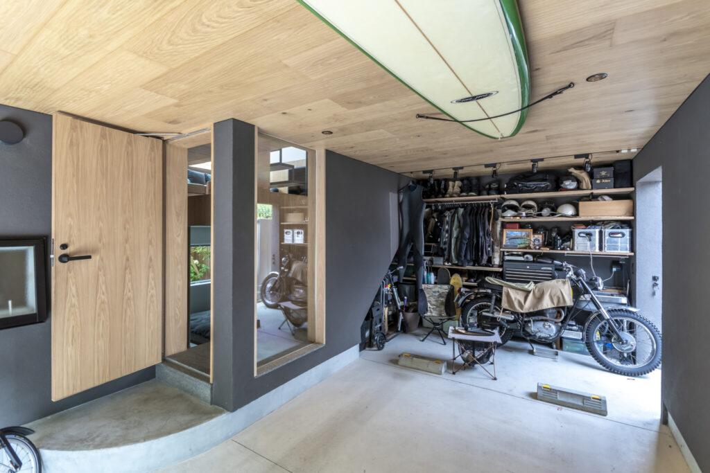 """ガレージの奥は賢さんの""""秘密基地""""。趣味のバイクやサーフボードのお手入れ、キャンプの準備など休日はここで過ごすことが多いそう。室内から続く浮造り仕上げの天井が贅沢。"""