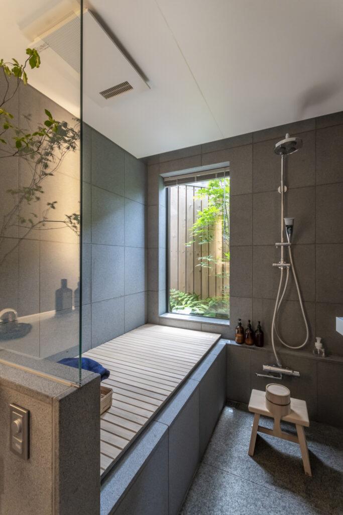 前庭へと抜けを造ったバスルーム。趣のある檜の風呂蓋はふるさと納税の返礼品で、オーダーメイドしたもの。