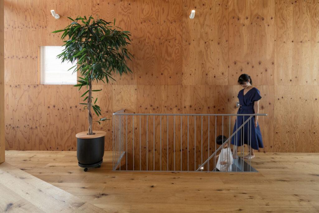 構造用合板の壁に浮かぶ階段の手すりのシンプルなデザインが美しい。「壁は将来的に色を塗ったり、プロジェクターを投影することも考えています」