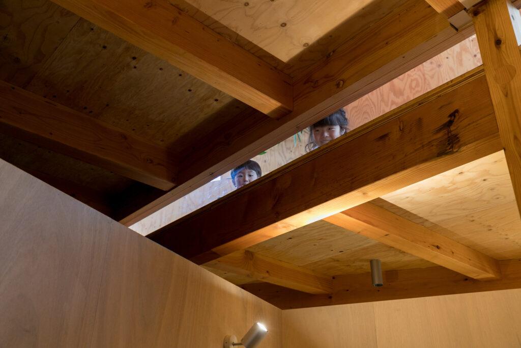 子どもたちが覗いているのは、2階の床の段差を利用して1階に光を取り込むスリット。この隙間を通して、2階と1階にいる家族の気配が感じられる。