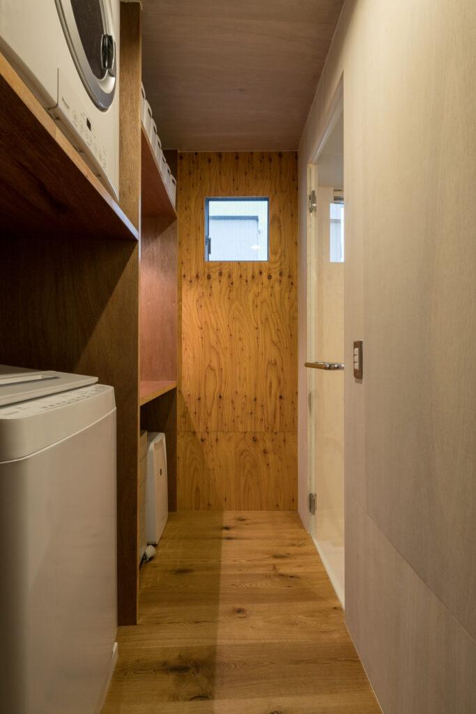脱衣室。右手がバスルーム。「洗濯機の上のガス乾燥機はなくてはならないものになりました。洗濯物を干す手間が省けます」