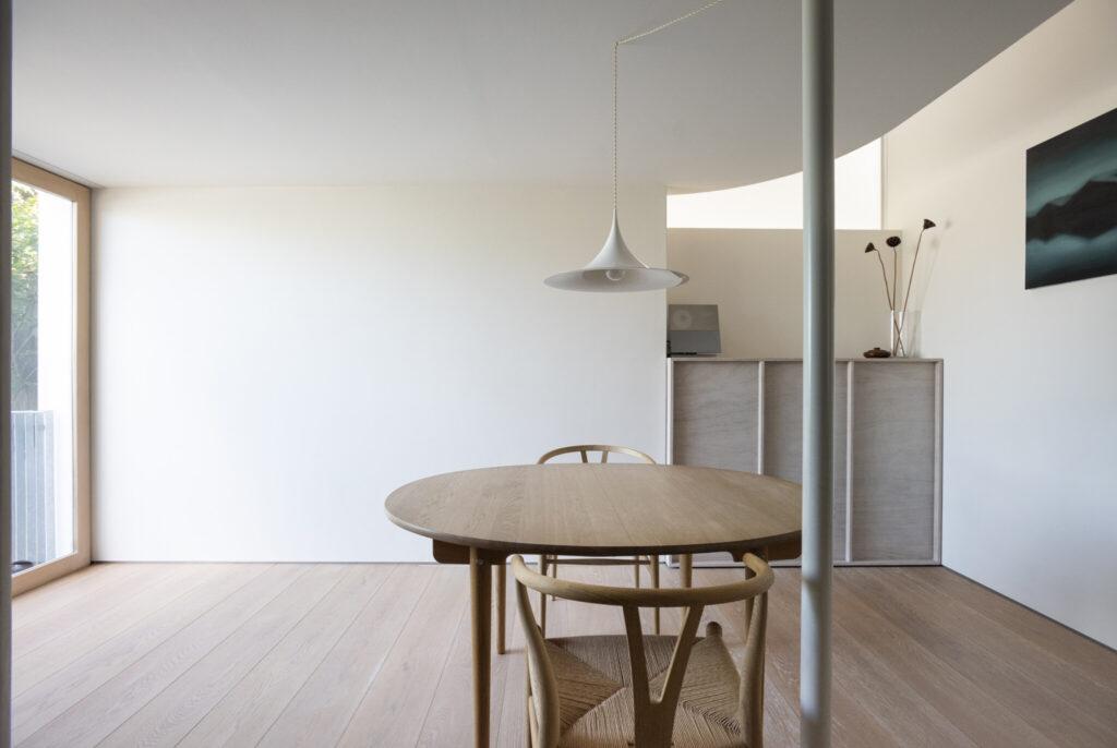 南西(右側)の隅に設けた吹き抜けは、曲線を描く天井により幻想的な雰囲気。『カール・ハンセン&サン』の丸いダイニングテーブルとYチェアがシンプルな空間を引き立てる。