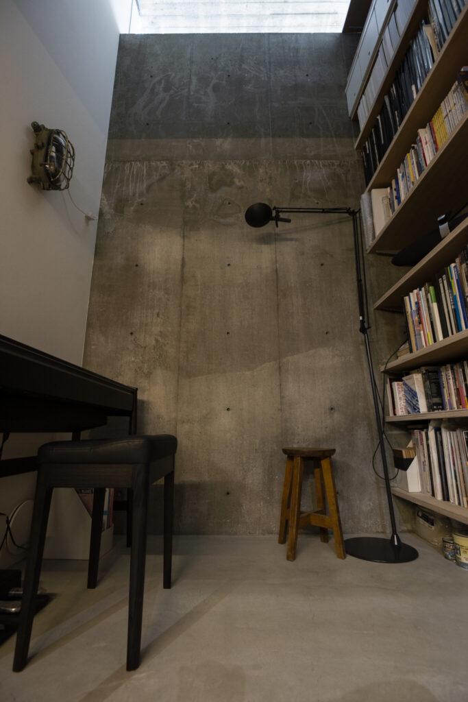 地下2階から地下1階へと続く吹き抜けと本棚。地下1階の高窓から光を取り込んでいる。