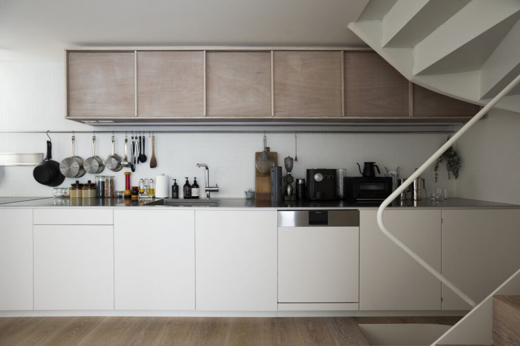 壁一面を使用した5.5mのキッチン。料理好きの綾夏さんが使い勝手を考えて図面を描き、家具屋にオーダー。「『GAGGENAU』の食洗器は絶対に入れたかった」と綾夏さん。