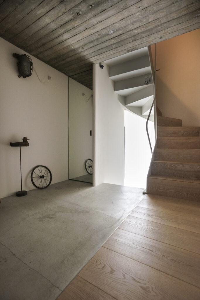 地下1階に位置する玄関ホール。キッチンと同様に、コンパクトな家に対してあえて広々とした玄関スペースに。くもりガラスの玄関の扉からやわらかな光が射す。