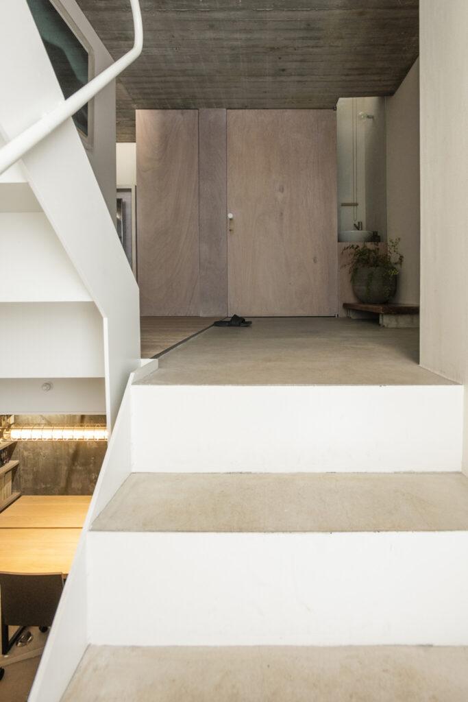 玄関を入ると階段の踊り場に。玄関ホールの奥の扉内は、靴のまま使用できるトイレ。右側の手洗い場は明り取りの役目も。