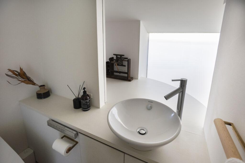1階から続く吹き抜けを介して、2階のトイレと左奥の寝室へと光が届く。隣家が迫っているため、窓はくもりガラスを採用。
