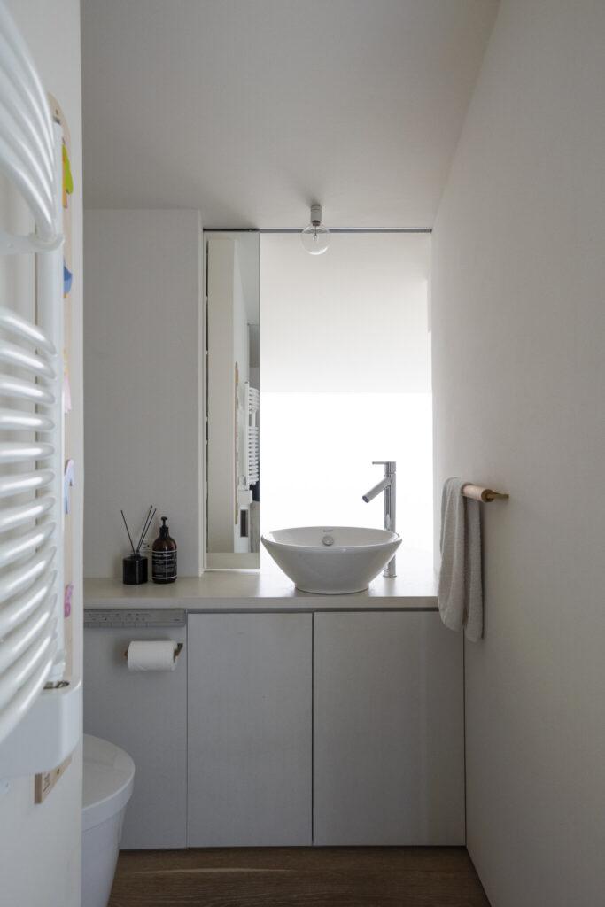 2階トイレの洗面所の鏡は、スライド式で出し入れ自在。開けると、奥の吹き抜けから光が射し込む。