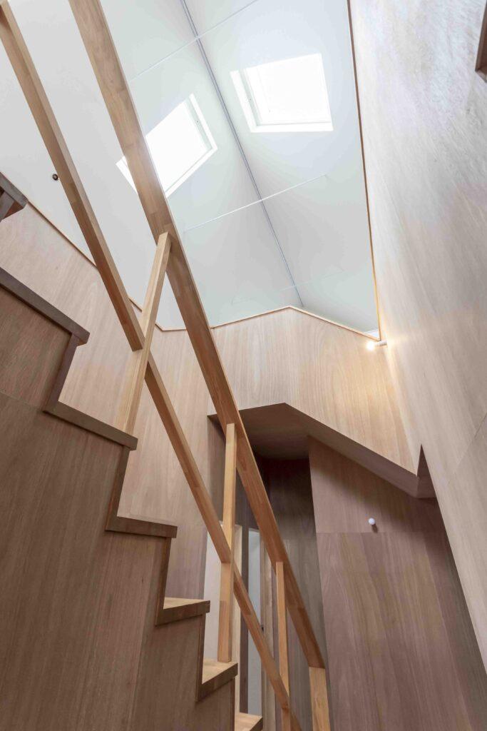 2階の天窓からの光が、吹き抜けを介して玄関ホールにも差し込む。玄関ホールにはラワン材などの木材をふんだんに使用し、木の温かみが感じられる。階段下には、ご主人、長女、長男のそれぞれの個室を配置。
