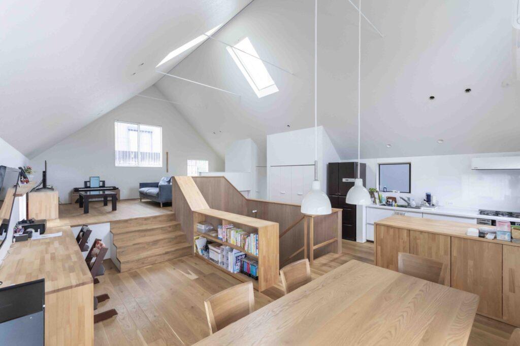 吹き抜けのホールを中心にキッチンやダイニング、リビング、造作の本棚、スタディコーナーなどの各機能を配置し、ぐるりと動き回れる回遊性のある空間を実現。床材には黄色いオーク材を使用。
