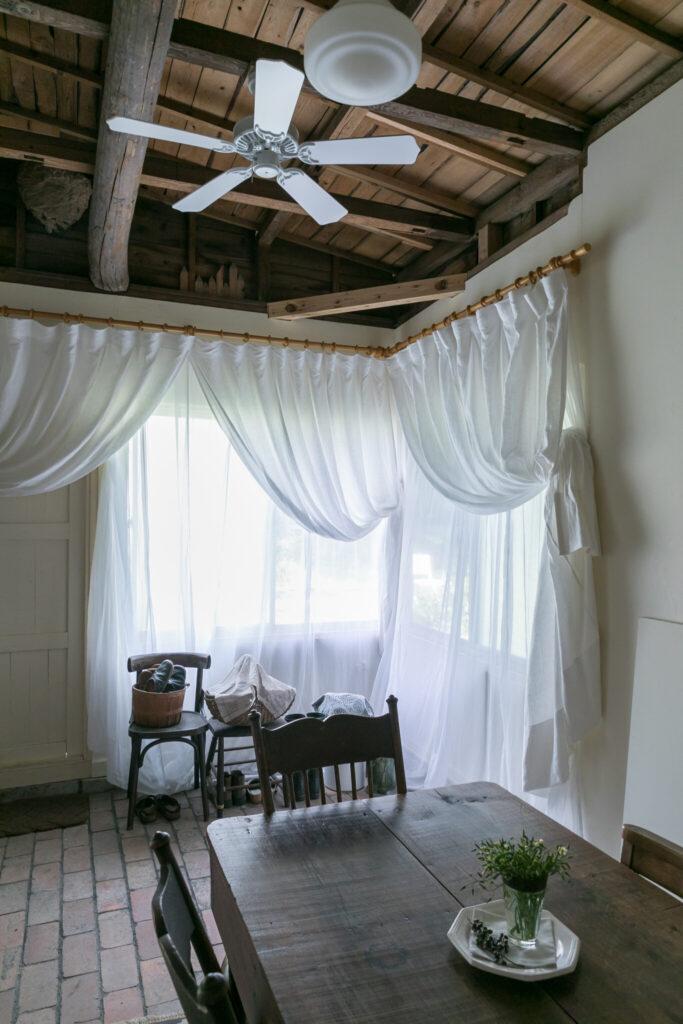 「アメリカに住んでいた頃旅したマルティニークの宿で、カーテンをこんなふうにサイドのフックにまとめていました。いつかやってみたいと思っていたことのひとつです」。手持ちのカーテンレールを生かすため、麻とオーガンジーの2枚のカーテンを上部で縫い合わせた。